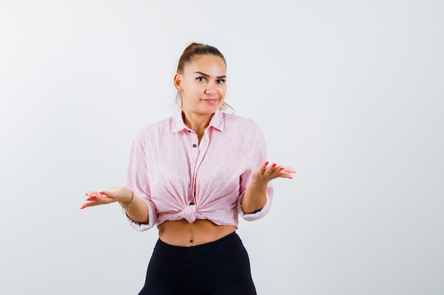 Young lady in shirt, pants showing helpless gesture and looking confused