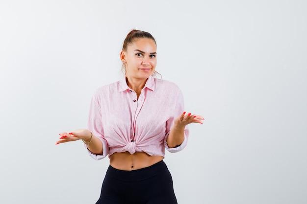 Giovane donna in camicia, pantaloni che mostrano gesto impotente e che sembra confusa
