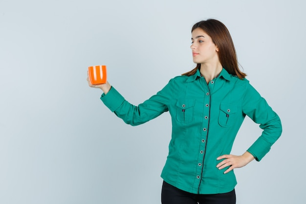 Young lady in shirt posing while holding orange cup of tea and looking confident , front view.