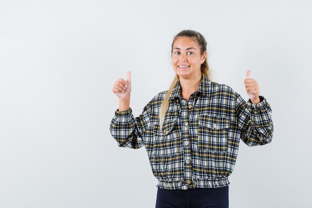 Giovane donna in camicia, pantaloncini che mostrano il doppio pollice in alto e che sembra felice, vista frontale.