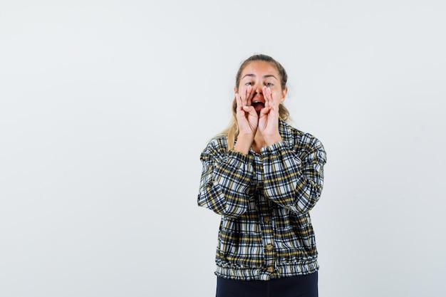 Giovane donna in camicia, pantaloncini che raccontano il segreto o che annunciano qualcosa, vista frontale.