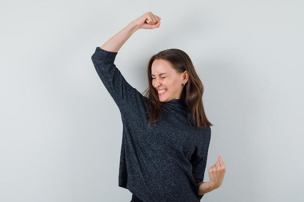 Giovane donna in camicia che mostra il gesto del vincitore e sembra fortunato