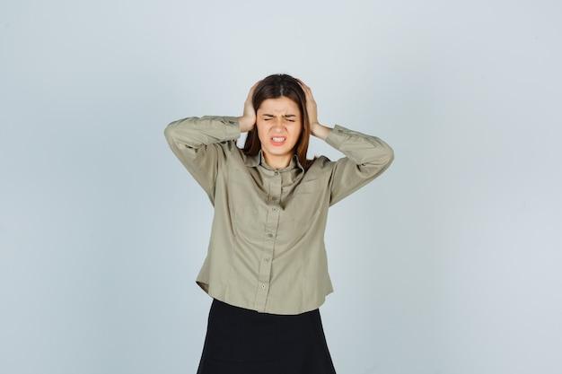 Giovane donna in camicia, gonna stringendo la testa con le mani e guardando infastidito
