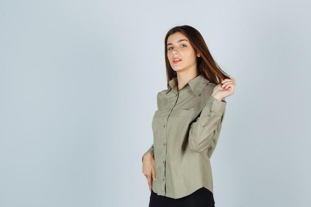 Giovane donna in camicia, gonna che gioca con i suoi capelli e sembra sicura, vista frontale.