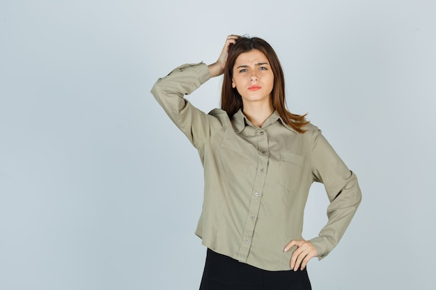 Giovane donna in camicia, gonna che si gratta la testa mentre si acciglia e sembra perplessa, vista frontale.
