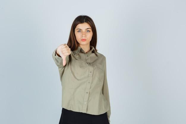 Giovane donna in camicia, gonna che mostra il pollice verso il basso e sembra delusa, vista frontale.