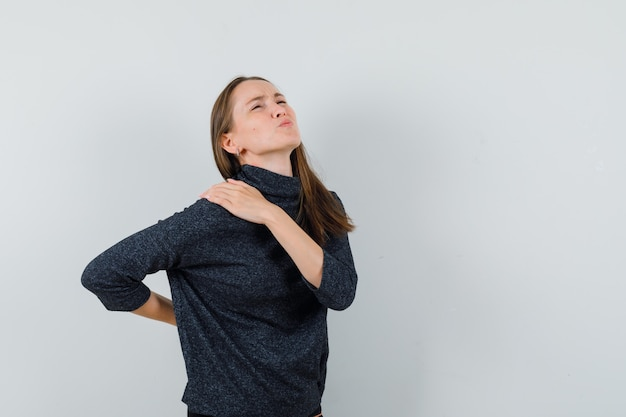 Young lady in shirt suffering from backache and looking fatigued