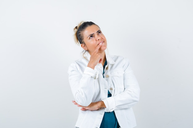 Young lady in shirt, white jacket with finger on mouth and looking pensive , front view.