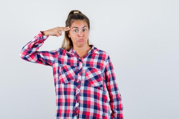 Молодая леди стреляет в себя из ручного пистолета в клетчатой рубашке и выглядит нерешительно, вид спереди.