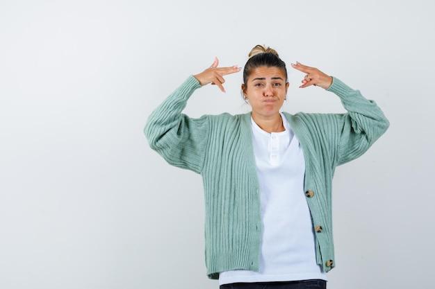 젊은 여성이 티셔츠, 재킷을 입고 뺨을 불고 웃기게 보이면서 권총으로 자신을 쏘고 있다