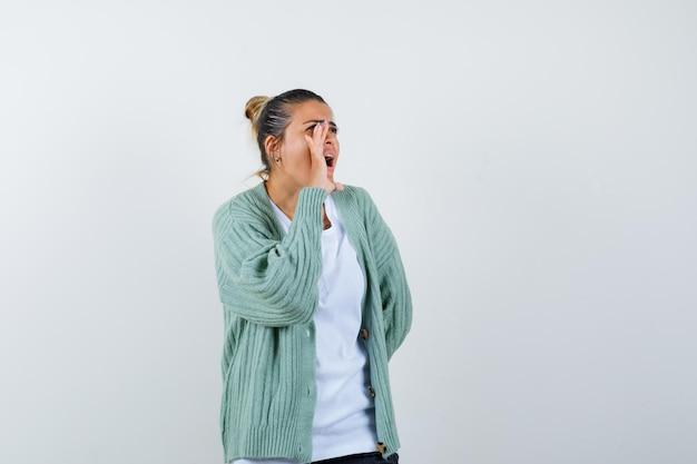 Девушка кричит в футболке, куртке и выглядит уверенно