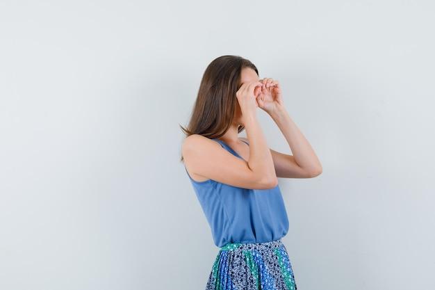 Молодая дама показывает бинокулярный жест, глядя в блузку, юбку и выглядит сосредоточенным. передний план.