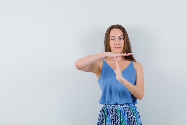 파란색 블라우스, 치마 및 심각한 찾고있는 제스처를 보여주는 젊은 아가씨. 전면보기.