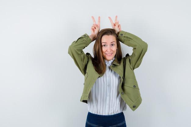 Молодая дама показывает жест ушей кролика в рубашке, куртке и выглядит смешно. передний план.