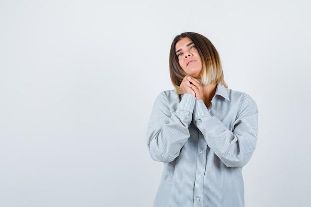 Молодая дама в огромной рубашке показывает сложенные руки в умоляющем жесте и выглядит обнадеживающей. передний план.