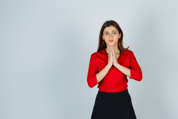 Young lady showing clasped hands in pleading gesture in red blouse