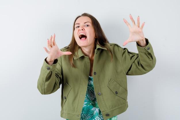 녹색 재킷에 고양이를 모방하고 공격적인 찾고 발톱을 보여주는 젊은 아가씨. 전면보기.