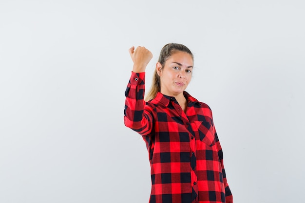 Giovane signora che mostra il pugno chiuso in camicia controllata e che sembra sicura