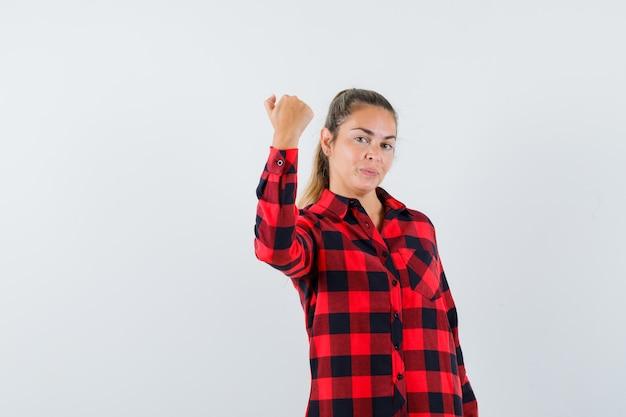 チェックシャツでくいしばられた握りこぶしを示し、自信を持って見える若い女性
