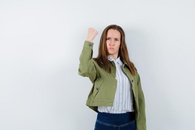 シャツ、ジャケットでくいしばられた握りこぶしを見せて、意地悪に見える若い女性。正面図。