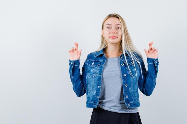 티셔츠, 데님 재킷, 스커트에 교차 손가락을 보여주는 젊은 아가씨와 귀여운 찾고