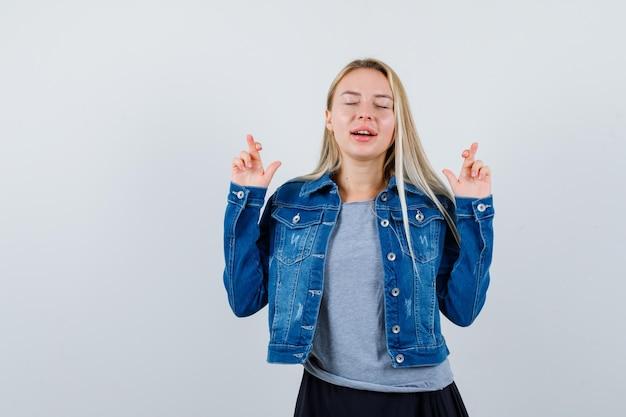 Giovane donna che mostra le dita incrociate in maglietta, giacca di jeans, gonna e sembra carina