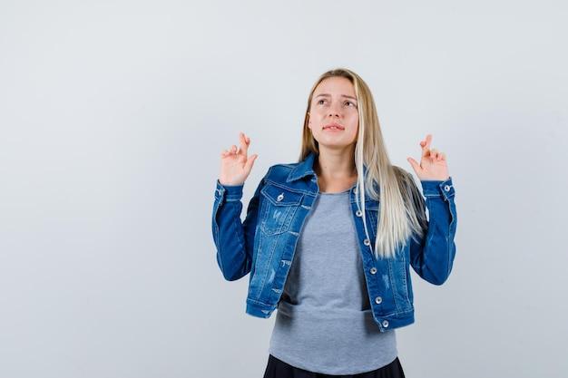 Giovane donna che mostra le dita incrociate in t-shirt, giacca di jeans, gonna e sembra premurosa.