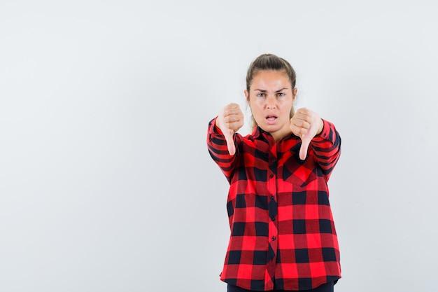 チェックのシャツを着て二重の親指を下に見せて、暗いように見える若い女性