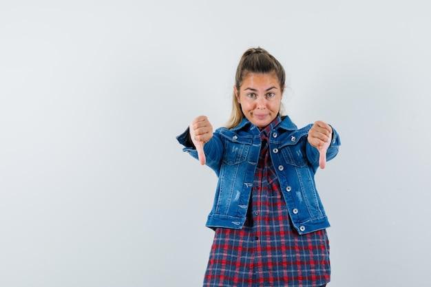 シャツ、ジャケット、自信を持って、正面図で二重親指を示している若い女性。