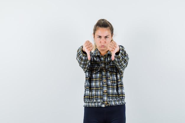 젊은 아가씨 셔츠, 반바지 아래로 두 엄지 손가락을 보여주는 우울한, 전면보기.