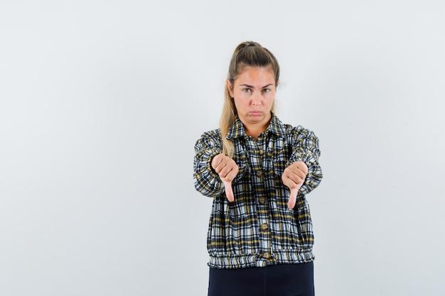Giovane donna che mostra i doppi pollici verso il basso in camicia, pantaloncini e sembra triste. vista frontale.