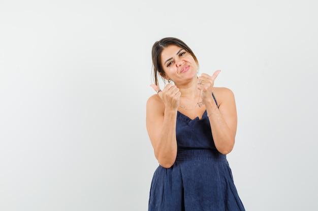 Giovane donna che mostra il doppio pollice in alto nel vestito e sembra allegra