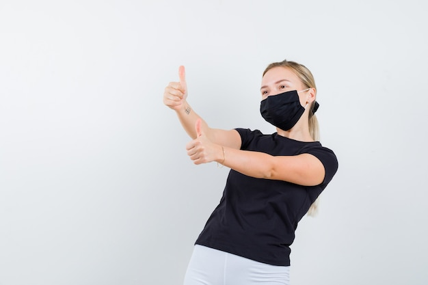 검은 t- 셔츠, 마스크 및 행복을 찾고 두 엄지 손가락을 보여주는 젊은 아가씨. 전면보기.