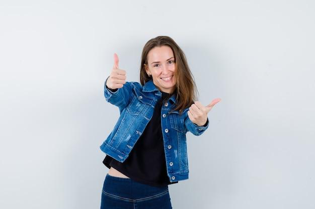 ブラウスで二重の親指を示し、自信を持って見える若い女性。正面図。