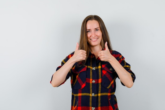 Молодая леди показывает двойные пальцы вверх в повседневной рубашке и выглядит веселой, вид спереди.