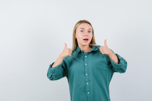 Молодая леди показывает двойные пальцы вверх в зеленой рубашке и выглядит счастливой