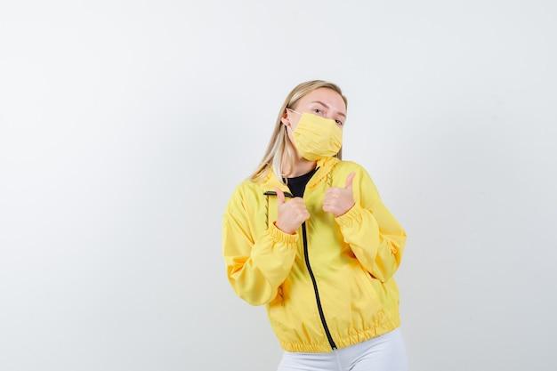 ジャケット、ズボン、マスクで二重の親指を示し、自信を持って見える若い女性。正面図。