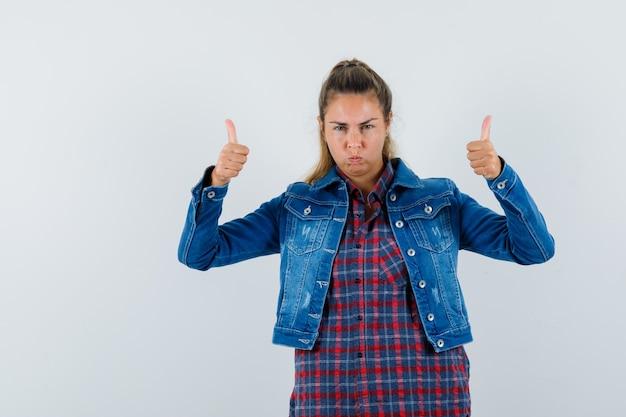 シャツ、ジャケットで二重の親指を示し、自信を持って見える若い女性。正面図。