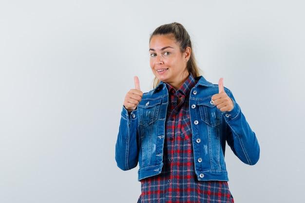シャツ、ジャケットで二重の親指を見せて、幸せそうに見える若い女性、正面図。