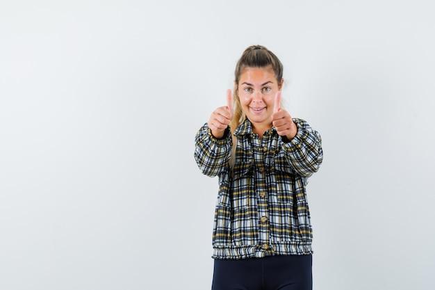 シャツ、ショートパンツで二重の親指を示し、自信を持って見える若い女性。正面図。