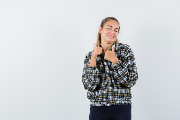 シャツ、ショートパンツで二重の親指を見せて、幸せそうに見える若い女性。正面図。