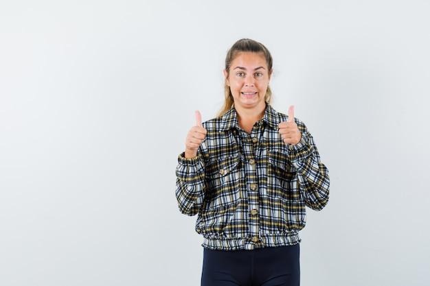 シャツ、ショートパンツ、陽気に見える、正面図で二重の親指を示す若い女性。