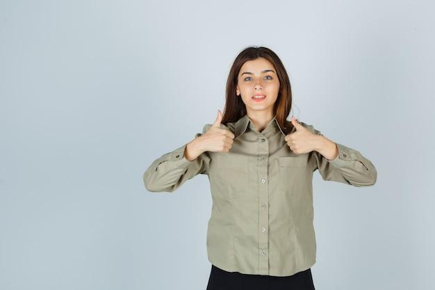 シャツ、スカートで二重の親指を見せて、幸せそうに見える若い女性。正面図。