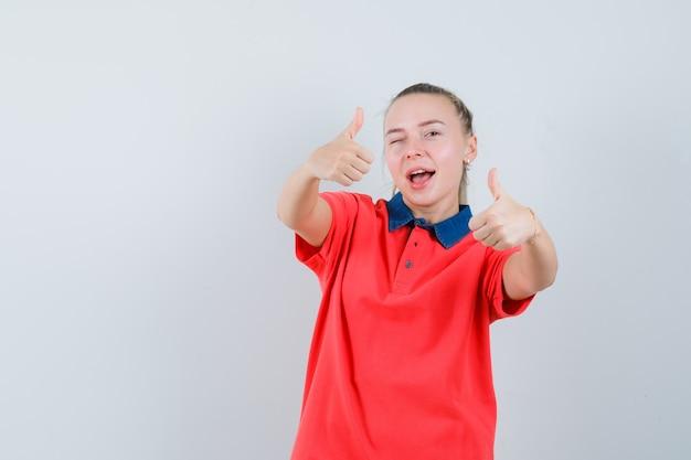 Giovane signora che mostra i doppi pollici in su in maglietta e che sembra felice