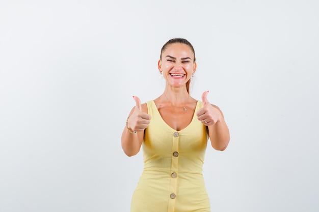 Giovane signora che mostra i doppi pollici in su in vestito giallo e che sembra felice, vista frontale.