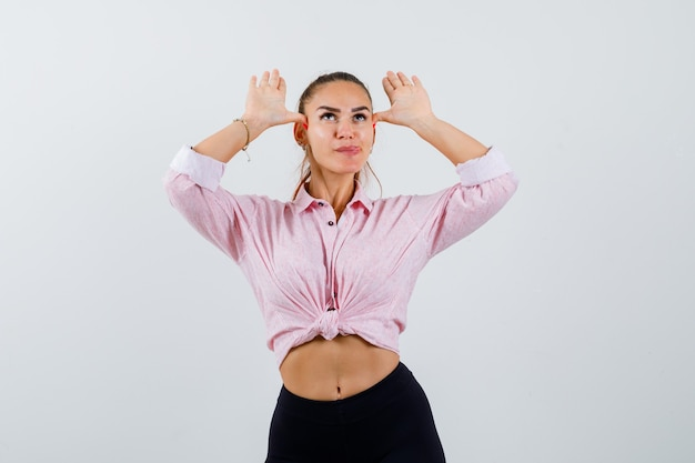 Young lady showing ears gesture in shirt, pants and looking funny