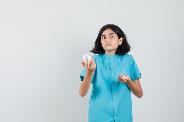 青いシャツを着た空の薬瓶を見せて、無力に見える若い女性。
