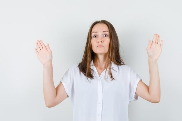 Молодая леди демонстрирует достаточно жестов в белой блузке и выглядит серьезно.