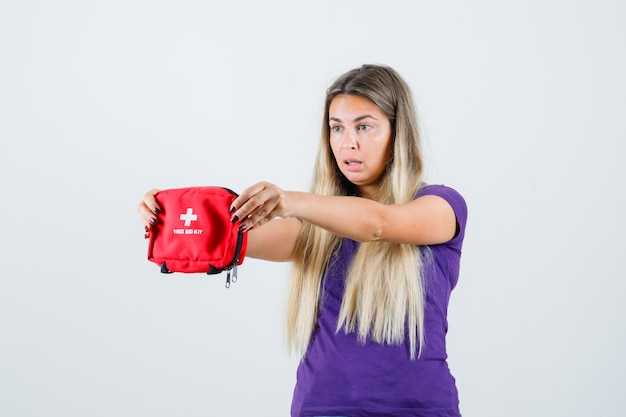Молодая дама показывает аптечку в фиолетовой футболке и выглядит удивленным, вид спереди.