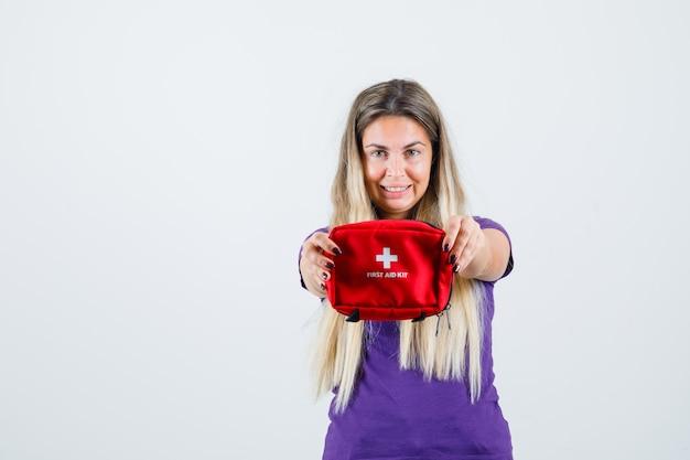 Giovane signora che mostra il kit di pronto soccorso in maglietta viola e sembra allegro. vista frontale.